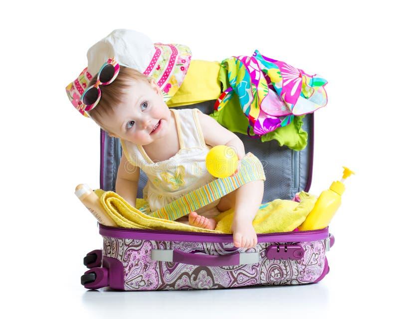 Baby, das im Koffer mit Sachen für Urlaubsreise sitzt lizenzfreie stockbilder