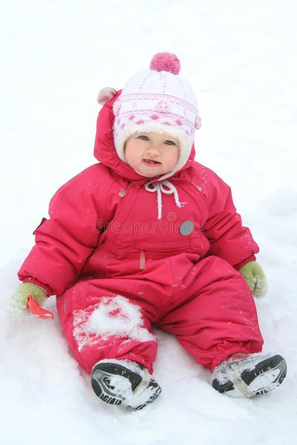 Baby, das im Schnee sitzt stockbilder