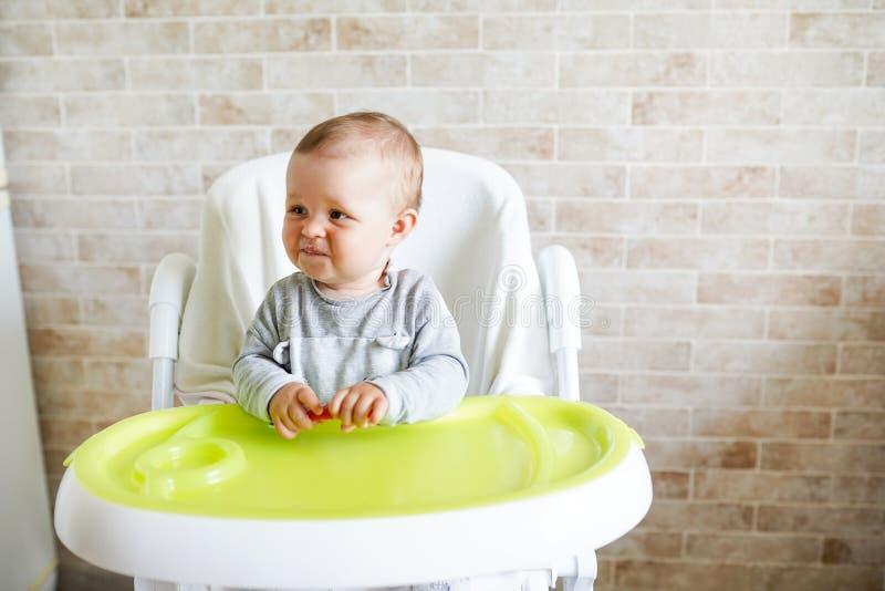 Baby, das im Stuhl in der sonnigen K?che sitzt Gesunde Nahrung f?r Kinder Kopieren Sie Platz lizenzfreies stockbild