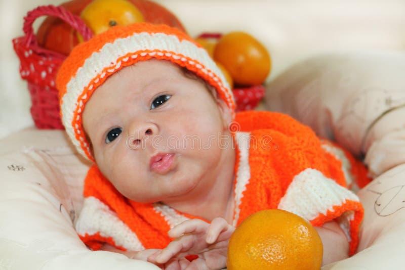 Baby, das Luftkuß sendet Porträt des neugeborenen Babys im orange knitte stockfoto