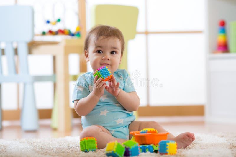 Baby, das mit bunten Plastikziegelsteinen auf dem Boden spielt Kleinkind, das Spaß hat und aus Erbauerziegelsteinen heraus errich stockbilder