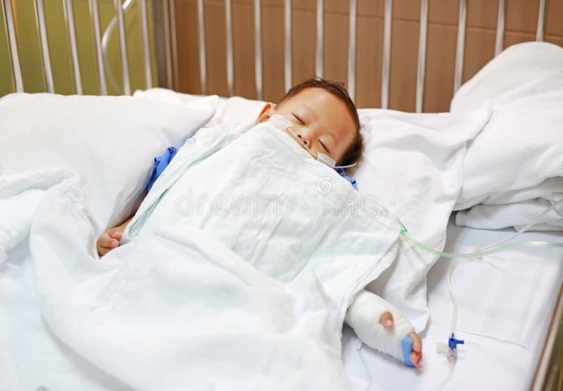 Baby, das mit der Befestigung des Venenkatheters, um auf Bett am Krankenhaus zu übergeben schläft Baby zugelassen am Krankenhaus  lizenzfreie stockfotografie