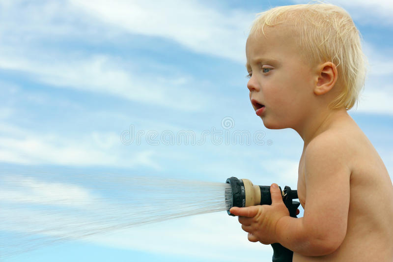 Baby, das mit Garten-Schlauch spielt lizenzfreies stockbild
