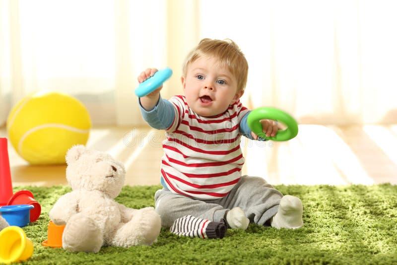 Baby, das mit Spielwaren auf einem Teppich spielt stockfoto