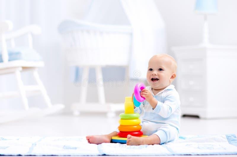 Baby, das mit Spielzeugpyramide spielt Kinderspiel stockfotografie