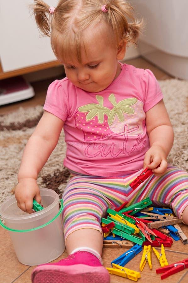 Baby, das mit Stöpseln spielt stockfotos