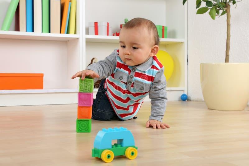 Baby, das mit Würfeln und Ziegelsteinen spielt lizenzfreies stockbild
