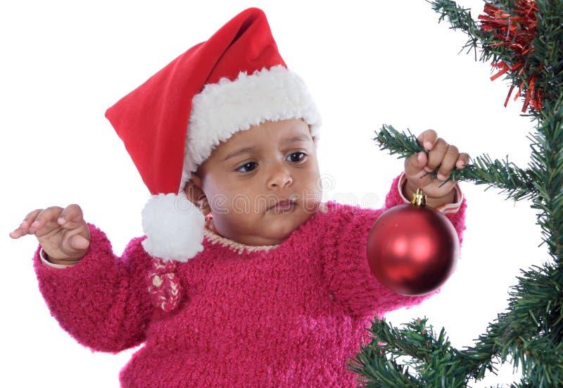 Baby, das mit Weihnachtsbaum spielt stockbild
