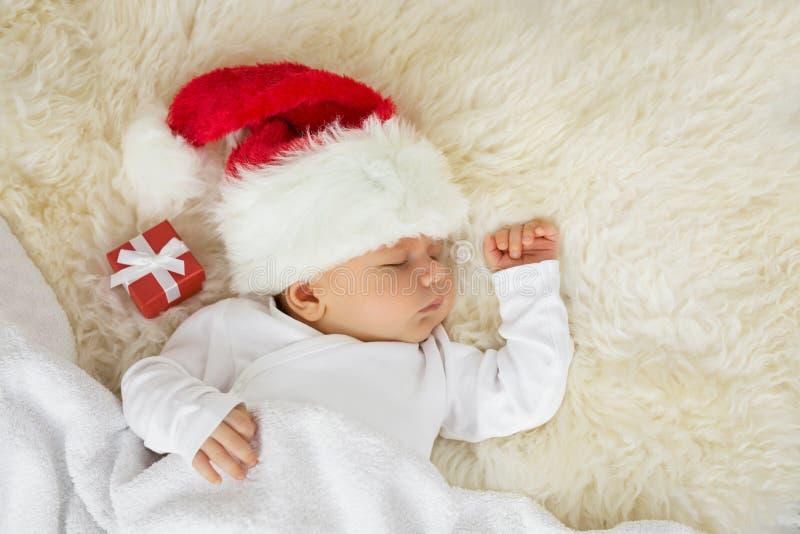Baby, das an mit Weihnachtshut und Geschenkbox schläft stockfoto