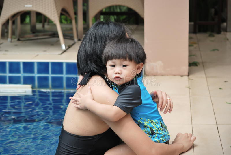 Baby, das Mutter im Pool umarmt lizenzfreies stockbild