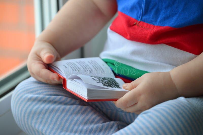 Baby, das oben ein Buch, dclose von den Händen Blätter treiben durch die Seiten liest lizenzfreies stockbild