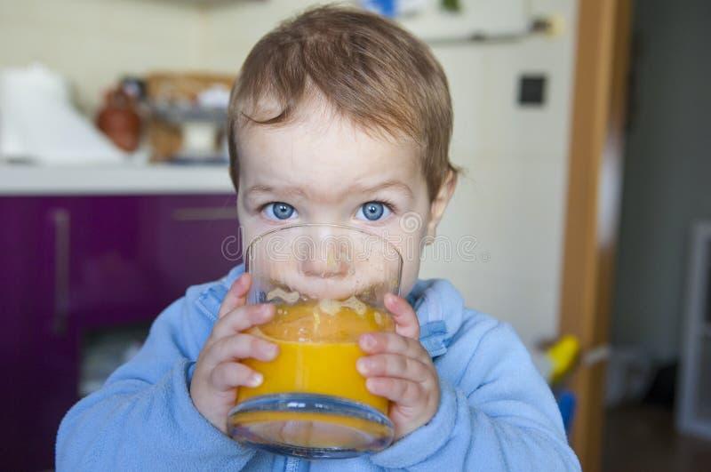 Baby, das orange frischen Saft trinkt lizenzfreie stockfotos