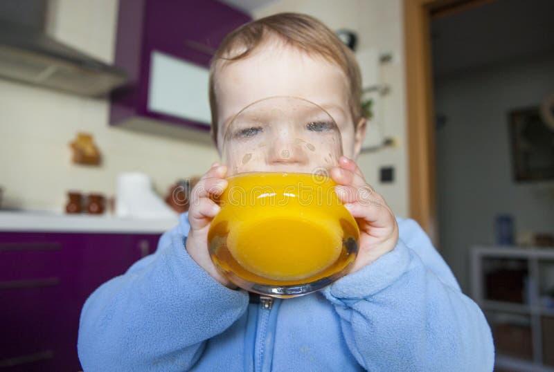 Baby, das orange frischen Saft trinkt stockfotografie