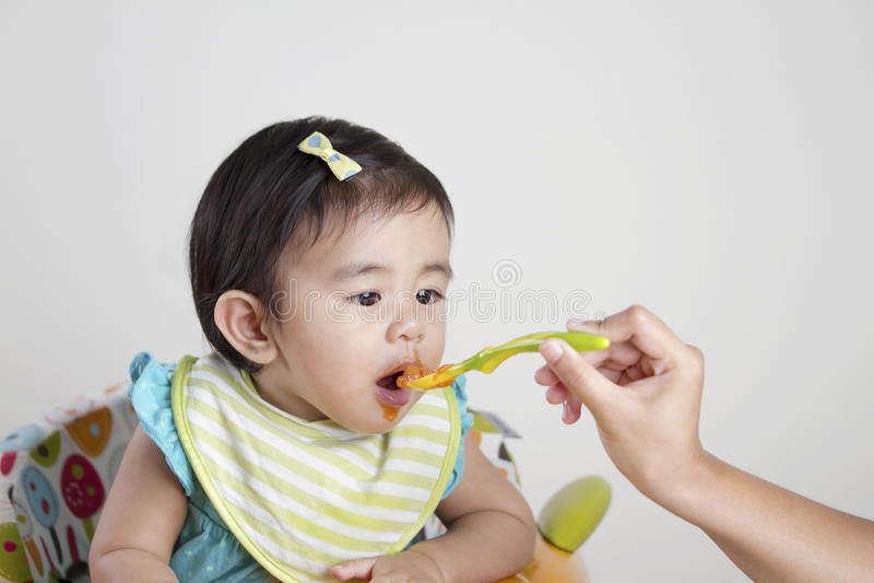 Baby, das Säuglingsnahrung isst stockbild