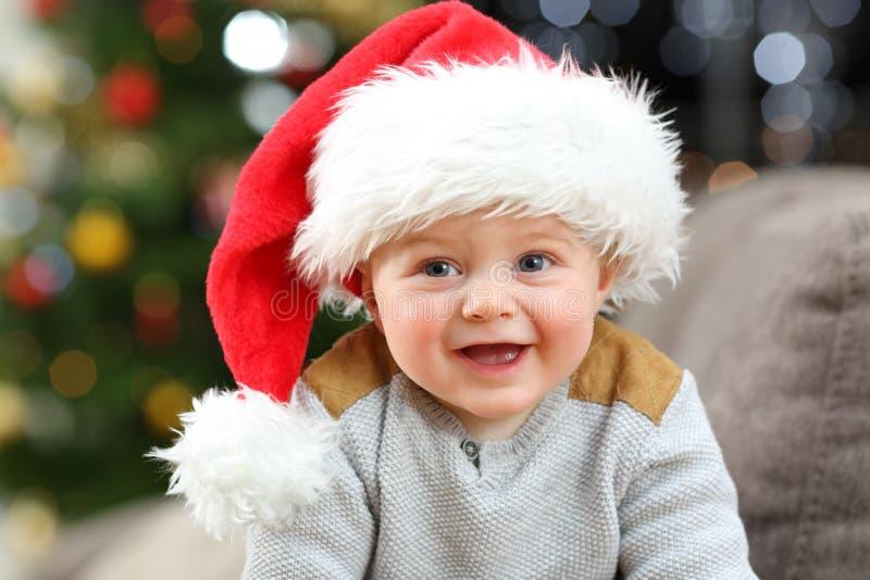 Baby, das Sankt-Hut zu Hause aufwirft im Weihnachten trägt lizenzfreies stockfoto