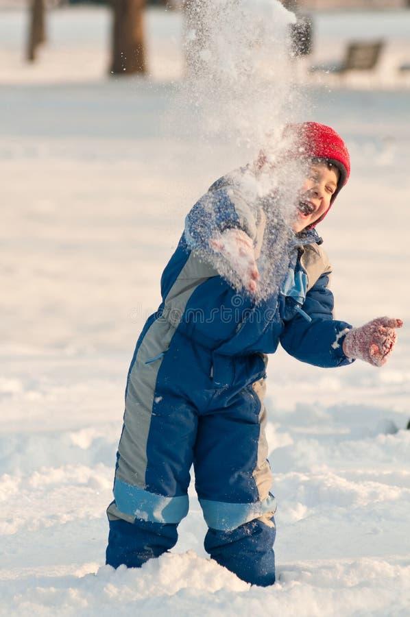 Baby, das Schneebälle zieht lizenzfreies stockbild