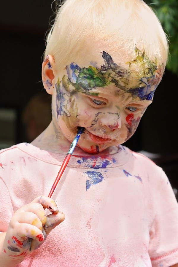 Baby, das sein Gesicht malt stockfotos
