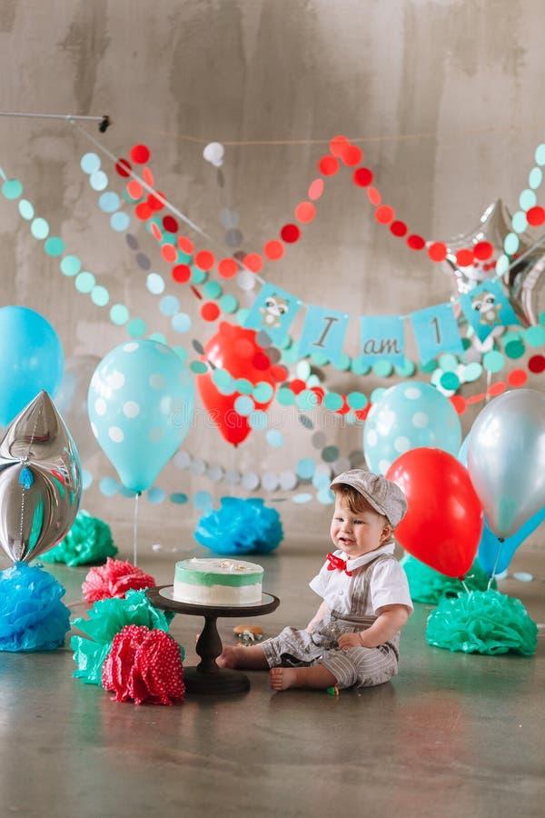 Baby, das seinen ersten Geburtstagskuchen berührt Herstellung des unordentlichen cakesmash in verziertem Studiostandort stockfoto