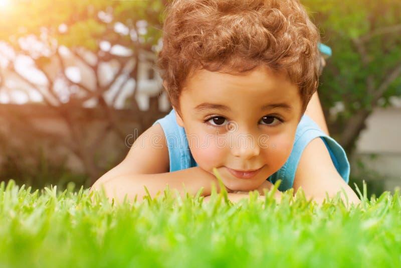Baby, das sich auf grünem Feld hinlegt stockfotografie