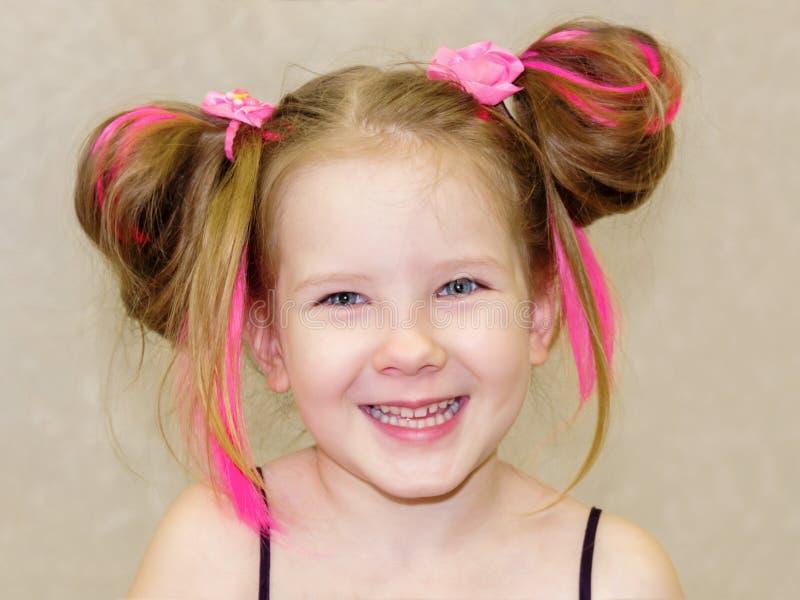 Baby, das Spaß mit ihrem rosa Haar hat stockfoto