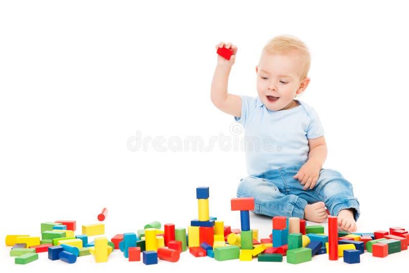 Baby, das Spielwaren-Blöcke, Kinderspiel-Mauerziegel, einjähriges Kind auf Weiß spielt stockfotos