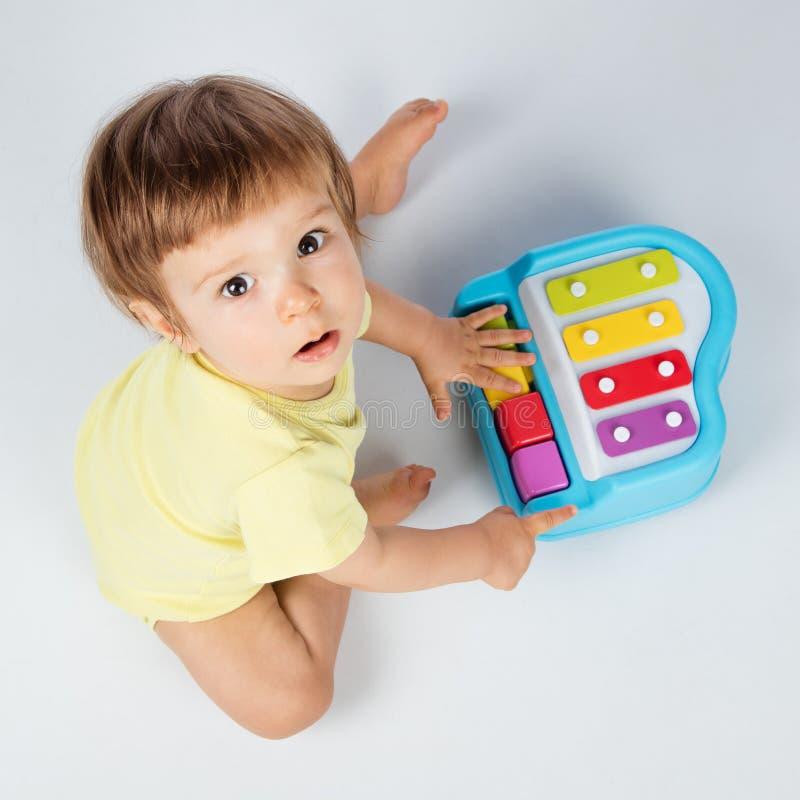 Baby, das Spielzeugklavier spielt stockbilder