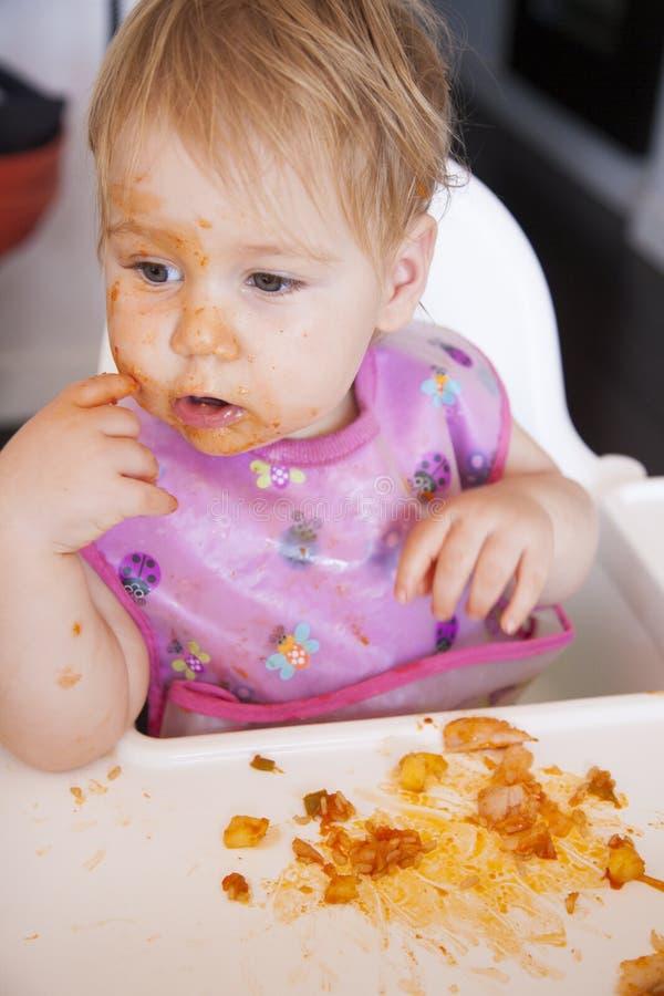 Baby, das Tomatenmahlzeit mit ihrer Hand isst stockfotografie