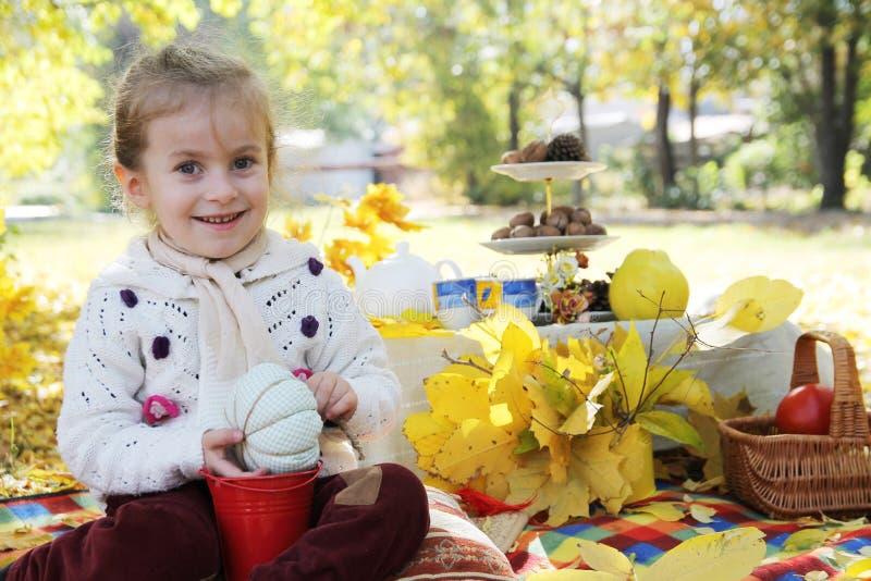 Baby, das unter Herbstbaum auf Picknick sitzt stockfotografie