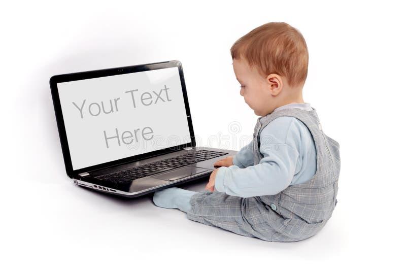 Baby, das vor einem Laptop sitzt lizenzfreies stockbild