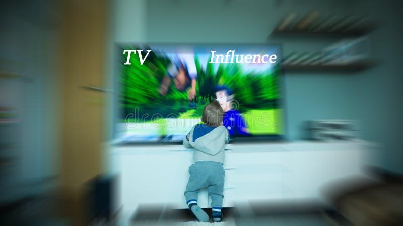 Baby, das vor großem Fernsehschirm steht stockbild