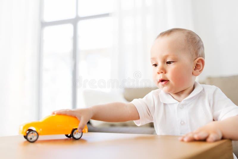 Baby, das zu Hause mit Spielzeugauto spielt lizenzfreies stockbild