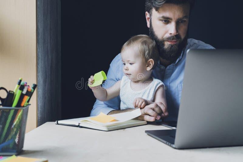 Baby dat op de knieën zit van de werkende ouder Vader werkt thuis en verzendt projecten online Pap zoekt vacatures op internet royalty-vrije stock afbeelding