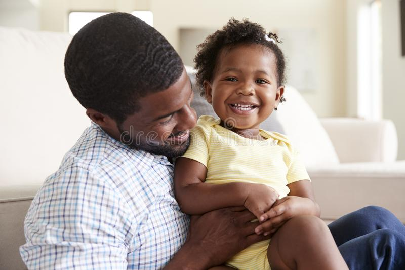 Baby Daughter Playing With Father On Sofa In Lounge At Home stock photo