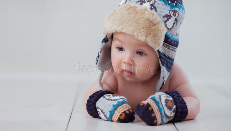 Baby in de winterhoed en vuisthandschoenen het liggen royalty-vrije stock foto's