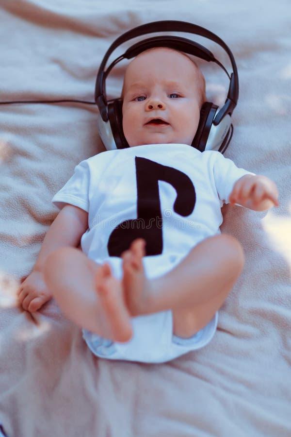Baby in den großen Kopfhörern, die auf Bett liegen stockbild