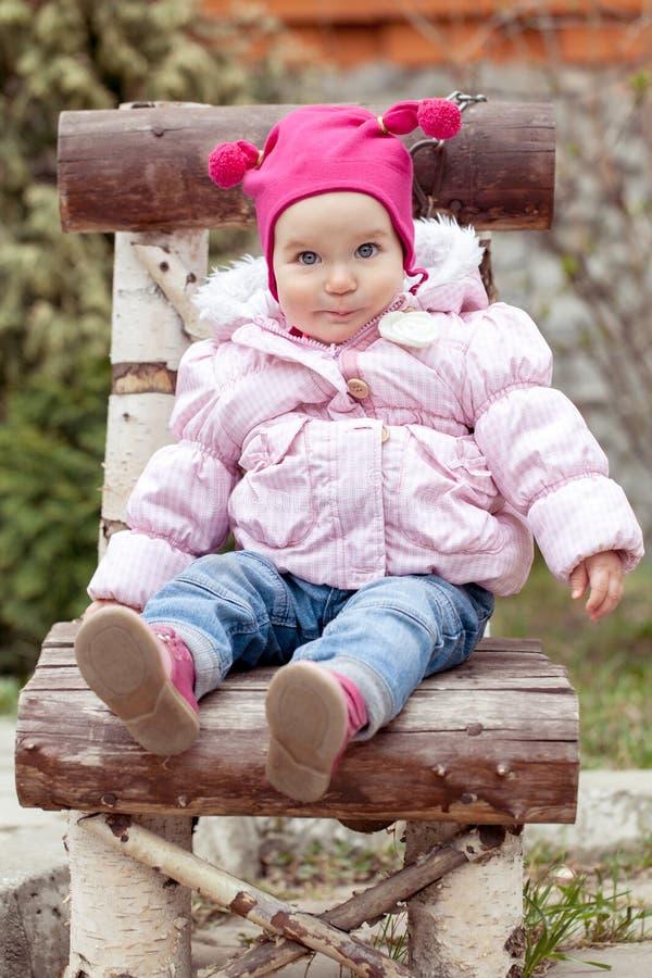 Baby in der rosa Jacke, die auf Holzstuhl sitzt stockfoto