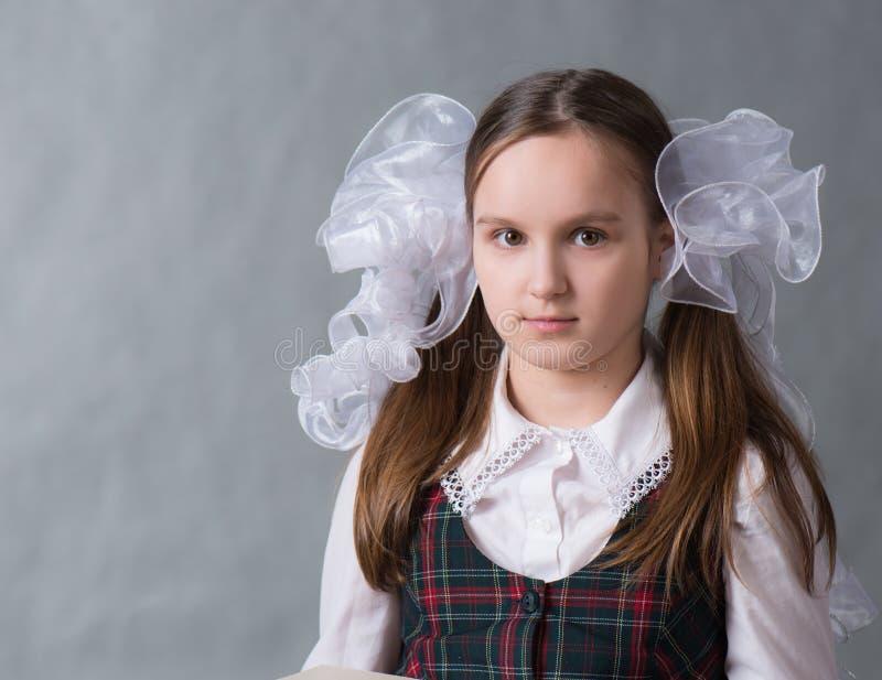 Baby in der Schuluniform mit weißen Bögen stockbilder