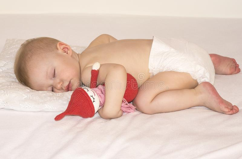 Sleeping baby in a diaper with a handmade toy royalty free stock image