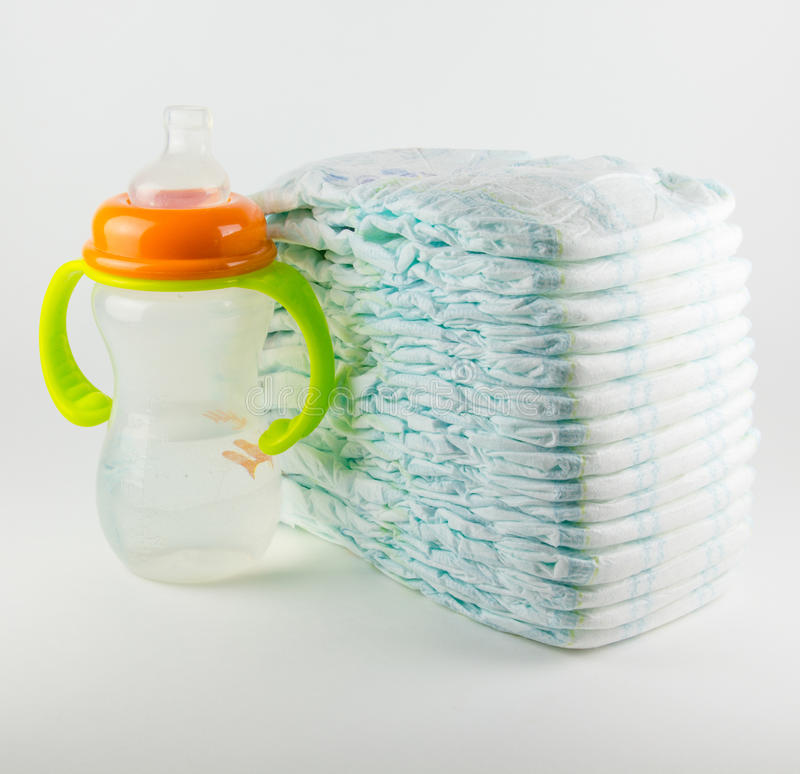 Baby diapers and bottle on a white background stock image