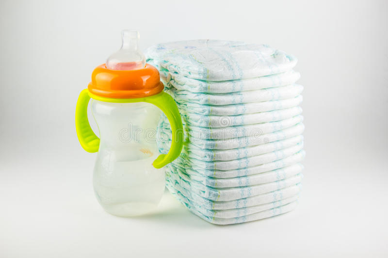 Baby diapers and bottle on a white background stock photo
