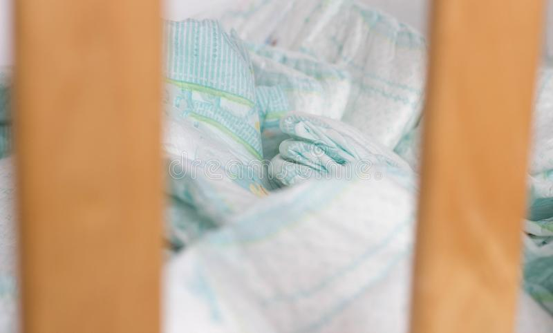 Baby diapers lie in a baby crib, close-up, diaper and baby cot. Baby diapers lie in a baby crib, close-up stock photo