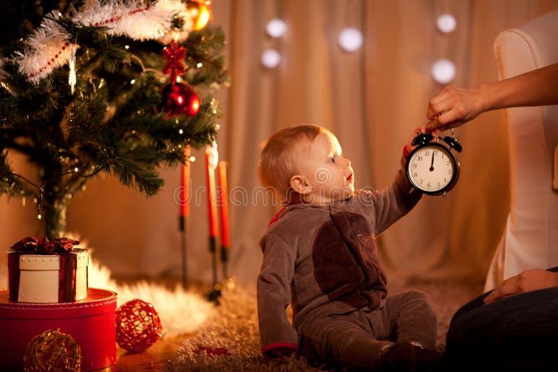 Baby dichtbij de holdingswekker van de Kerstboom royalty-vrije stock foto