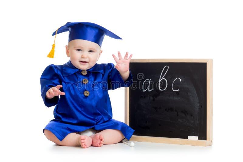 Baby die in academicuskleren bij bord zitten royalty-vrije stock foto