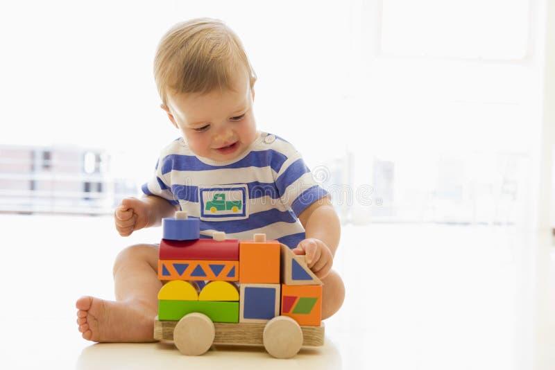 Baby die binnen met vrachtwagen speelt stock fotografie