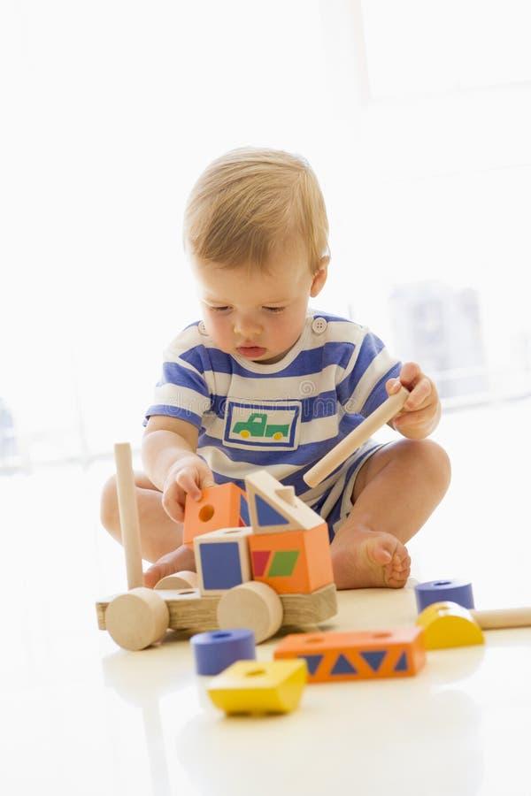 Baby die binnen met vrachtwagen speelt royalty-vrije stock foto's