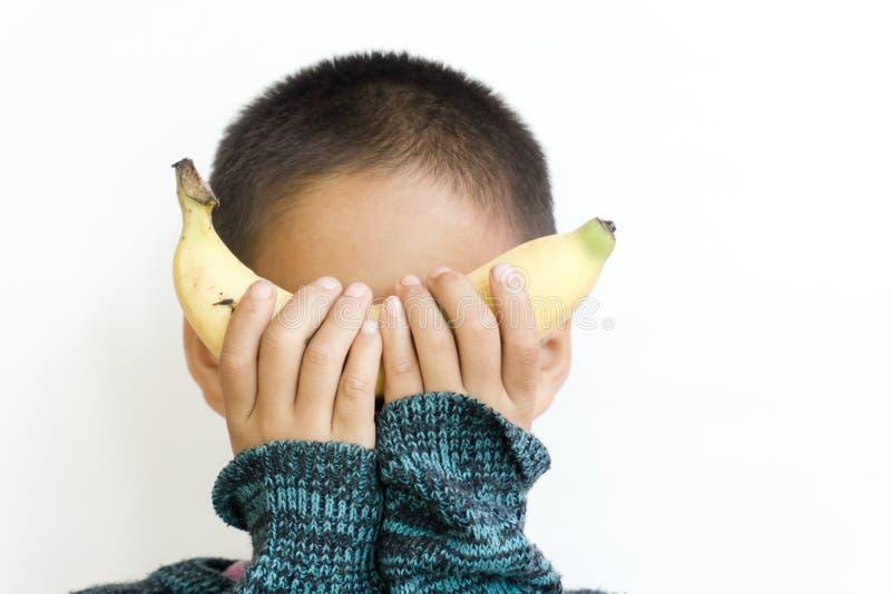 Baby die een banaan gesloten ogen zonder het gezicht houden te zien stock fotografie