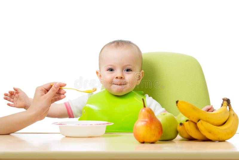 Baby die een lijsthoogtepunt van gezond voedsel hebben Vrolijke peuter met vruchten appelen, bananen, peer Geïsoleerd op wit stock foto's