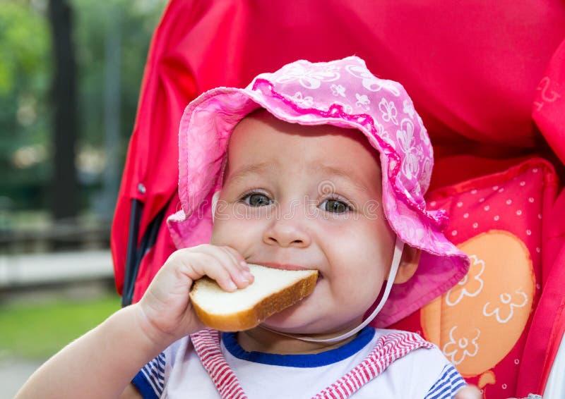 Baby die een stuk van brood eten stock fotografie