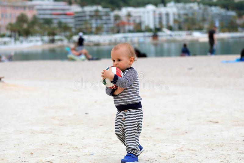 Baby die een Voetbalbal op Zand houden bij het Strand royalty-vrije stock afbeeldingen