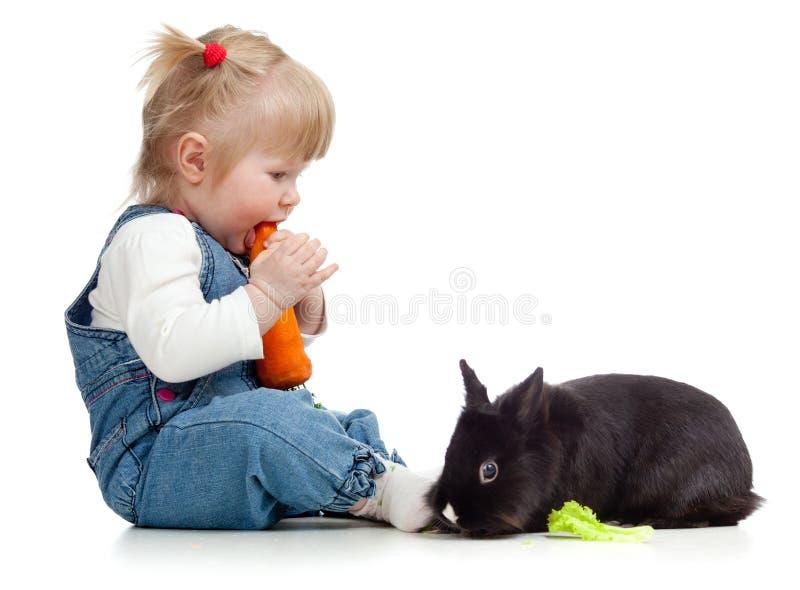 Baby die een wortel eet en konijn voedt stock fotografie